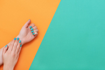 Perfect manicure with trendy nail art on orange and green background