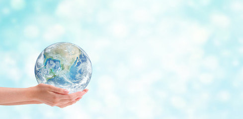 Ecology Concept : Hand holding blue planet earth globe with blurred bokeh background . (Elements of this image furnished by NASA.)