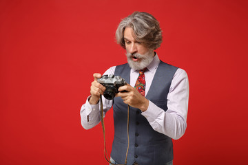 Amazed elderly gray-haired mustache bearded man in classic shirt vest colorful tie isolated on red background in studio. People lifestyle concept. Mock up copy space. Hold retro vintage photo camera.