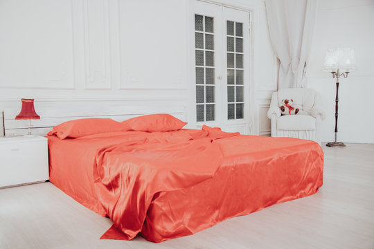 bed with red sheets in white bedroom Interior
