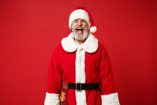 Frustrated elderly gray-haired mustache bearded Santa man in Christmas hat posing isolated on red background. New Year 2020 celebration holiday concept. Mock up copy space. Scream keeping eyes closed.