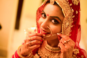 Beautiful female model in traditional indian bridal costume with heavy makeup and gold jewelery, indian bride portrait head shot