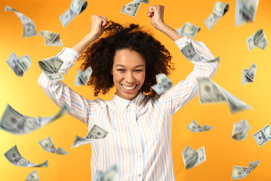 Happy African-American woman and falling dollar banknotes on color background