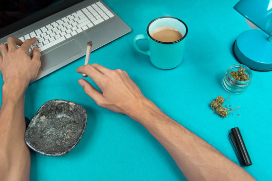 Person smoking a marijuana joint while working in a blue table with a computer and a coffee cup.