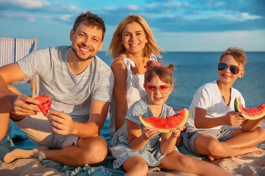 Portrait of happy family eating watermelon on sea beach