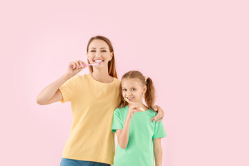 Fotomurales - Portrait of mother and her little daughter brushing teeth on color background
