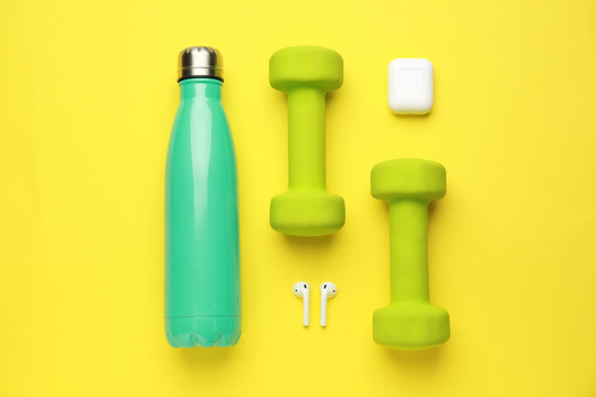 Sports water bottle, dumbbells and earphones on color background