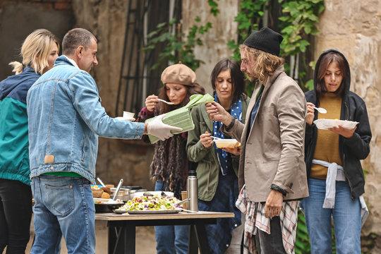 Volunteers giving food to homeless people outdoors