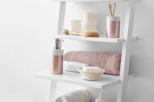 Body care cosmetics with accessories on shelves in bathroom