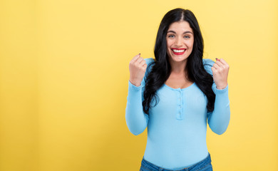 Successful young woman on a yellow background