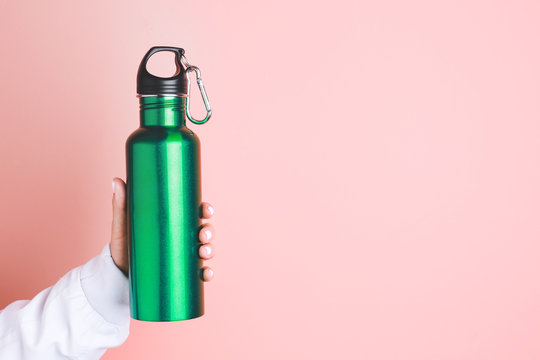 Female hand with sports water bottle on color background