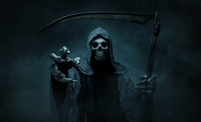 Grim reaper reaching towards the camera over dark, misty background with copy space