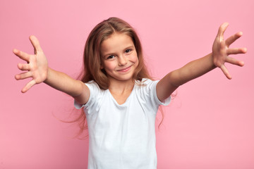 cheerful positive beautiful girl in white t-shirt with arms wide open looking at the camera, kid...
