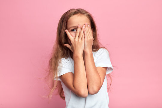 emotional little girl covers her face with her hand isolated over pink background, child watching horror film, movie, reaction, facial expression. isolated pink background
