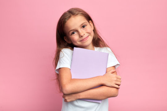 Little beautiful smiling girl holding book, going to school. close up portrait, isolated pink background, childhood. kid hugging a book. lifestyle, interest, hobby, free time, spare time
