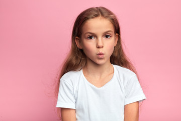 closeup portrait of serious little kid in white t-shirt with pursed lips and large eyes. kid staring at the camera . close up portrait, isolated pink background.
