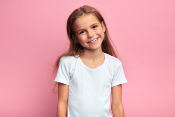 cheerful blonde girl in white T-shirt looking at the camera with positive expression. close up portrait, isolated pink background, studio shot