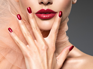 closeup face of a  woman with red nails and lips Wall mural