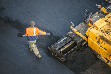 Workers lay a new asphalt coating using hot bitumen. Work of heavy machinery and paver. Top view