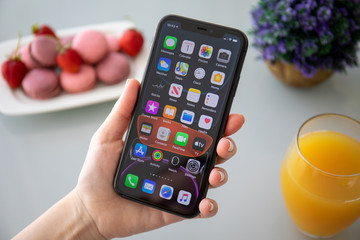Woman hand holding iPhone 11 with home screen IOS 13