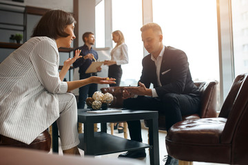 young successful woman in elegant stylish suit consulting a man at workplace. free consultation,...