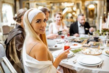 Elegant people having festive dinner at the restaurant Wall mural