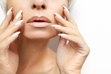 Portrait of a woman with clean healthy skin and a long manicure with milk nail Polish close-up.