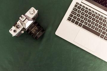 Camara retro , teclado de notebook y cuaderno sobre mantel verde