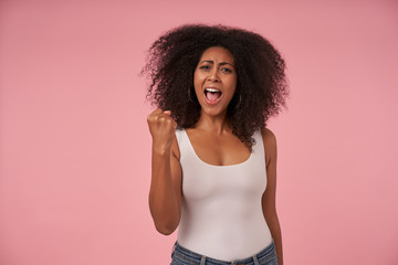 Happy young dark skinned lady casual with curly hairstyle wearing casual clothes, raising fist and looking at camera joyfully with wide mouth opened, isolated over pink background
