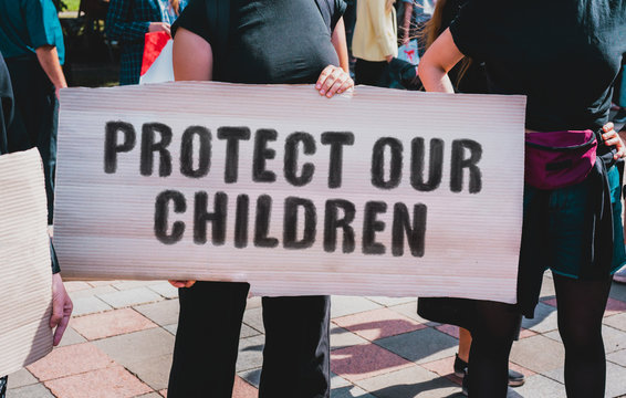 "The phrase "" Protect our children "" drawn on a carton banner in hand. A girl holds a cardboard with an inscription. Girls on the street. Protest. Human rights. Kids"