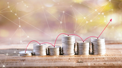 line graph up and down with touch coin on wooden table and green burred of nature backdrop, Finance concept.