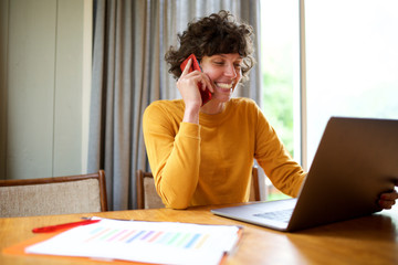 smiling woman working with laptop at home and talking with mobile phone Wall mural