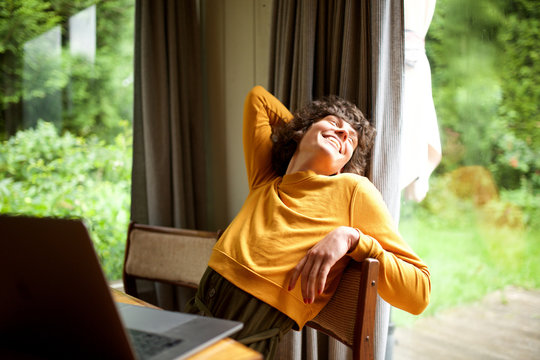 woman relaxing at home looking out of window