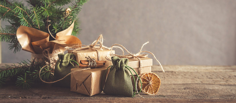 Christmas and zero waste, eco friendly packaging. Woman is wrapping gifts in craft paper on a wooden table, ecological Christmas holiday concept, eco decor