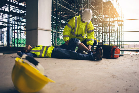 First aid support accident in site work, Builder accident fall scaffolding to the floor, Safety team help employee accident.