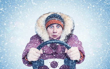 Frozen man in winter clothes drives a car in a snowstorm with his hands on the steering wheel, Front view.