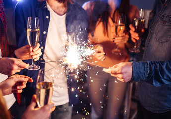 Group of happy people holding sparklers at party and smiling. Young people celebrating New Year together. Friends lit sparklers. Friends enjoying with sparklers in evening. Blur Background.