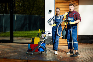 confident caucasian cleaners from cleaning service posing holding detergents, cleaning equipment. Look at camera, enjoy cleaner job. After successful work together. Background wooden big house