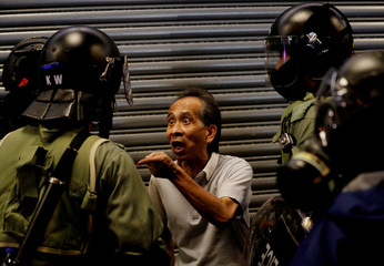 A pedestrian argues with riot police as he was asked to check his bag during an anti-government protest in Hong Kong