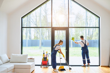 Young cleaners in blue uniform mopping wooden floor, cleaning big panoramic window, preparing country house for selling. Cleaning service concept