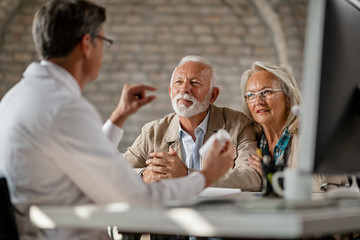 Mature couple talking to a doctor about supplement plans during a meeting.