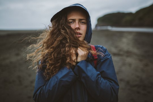 Curly model standing at the beach enjoying the cold autumn day with a hood on her head
