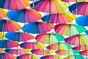 a collection of open umbrellas floating in the air, each umbrella is painted in all colors of the rainbow, photographed from below