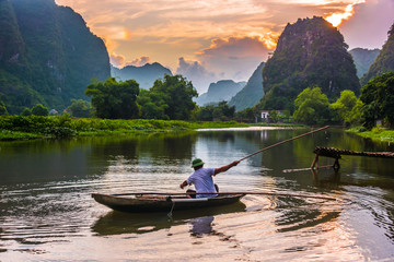 Fisherman on boat in Trang An, near Ninh Binh, Vietnam