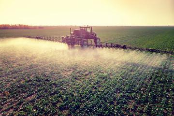 Tractor spraying fertilizer or pesticides on field with sprayer Fotoväggar