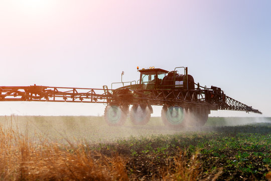 Tractor spraying fertilizer or pesticides on field with sprayer