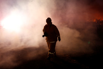 A photographer walks in a cloud of smoke during the wind-driven Kincade Fire in Healdsburg