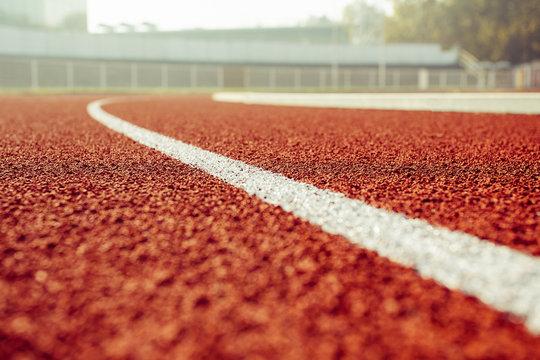 Empty red running track in stadium closeup