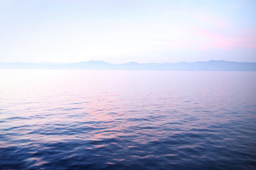 View of sunset over the calm ocean looking towards the horizon. Wall mural