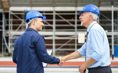 Fototapete - Two engineers shaking hands at a construction site